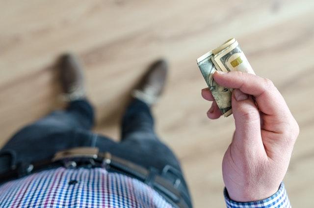 podnikatel drží peníze v ruce